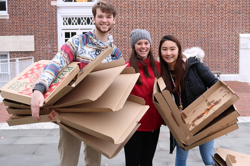 Three students hold empty pizza boxes and smile. They wear winter gear and stand in front of a brick wall.