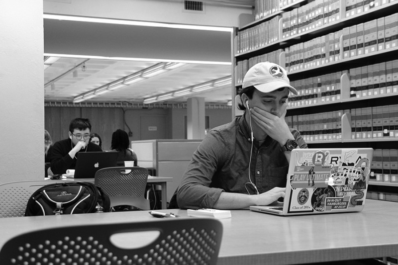 Black and white photo shows a stressed out student covering his mouth with his hand