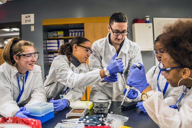 Five students clad in white lab gear and safety glasses wear blue rubber gloves. One girl smiles, they all stand around a table with lab equipment