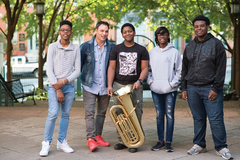 Four students and a teacher stand for a photo, one of the students holds a tuba