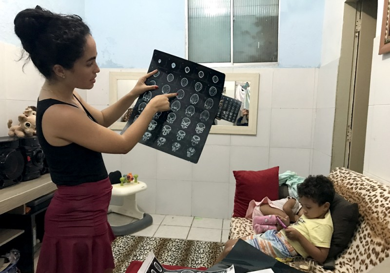 A woman holds a printout of brain scans and points to a spot on the chart while a baby is curled up on a couch next to her and a little boy plays with something in his hand