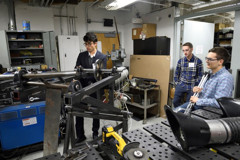Students in a machine lab demonstrate their device