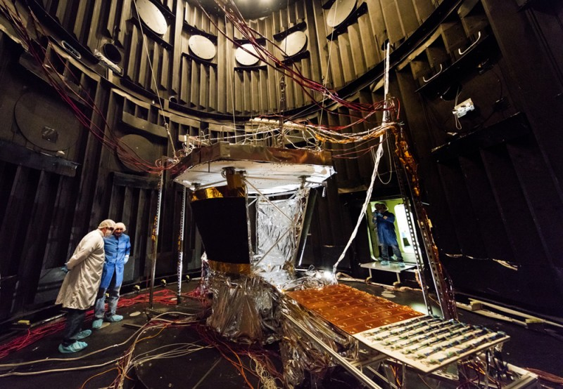 Four scientists test a spacecraft in a massive testing facility