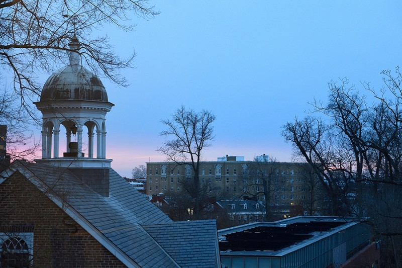 The sun rises in the distance while the Gilman bell tower is in the foreground