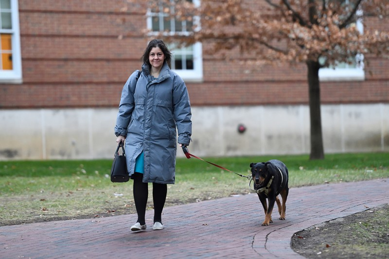 A woman in a puffy coat walks a rottweiler