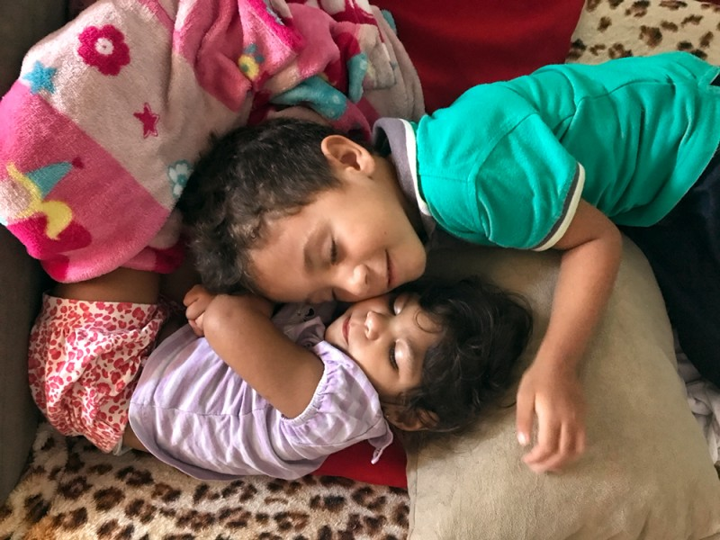 A little girl sleeps while a little boy lays his head down on a pile of pillows and blankets beside her. He smiles.
