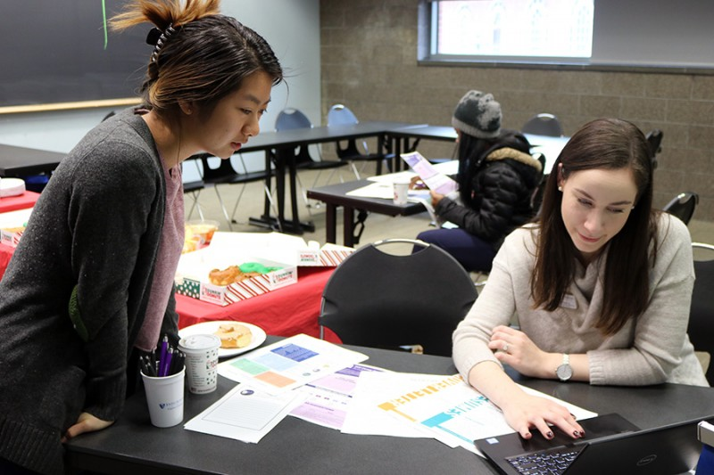 A student leans in to see a computer screen while a staff member show her a website. There are various papers on the table and a box of donuts in the background.