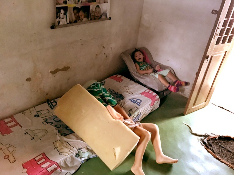 A little girl in a chair has her mouth open as if she's laughing while two boys wrestle on a mattress on the floor, although only their legs are visible