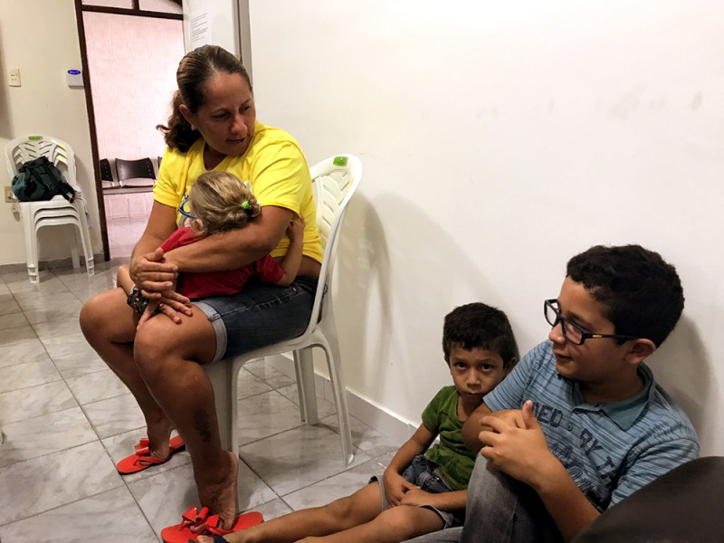 A woman holds a baby and sits on a white plastic chair in a kind of waiting room while two little boys sit on the floor; one little boy looks seriously or sadly at the camera