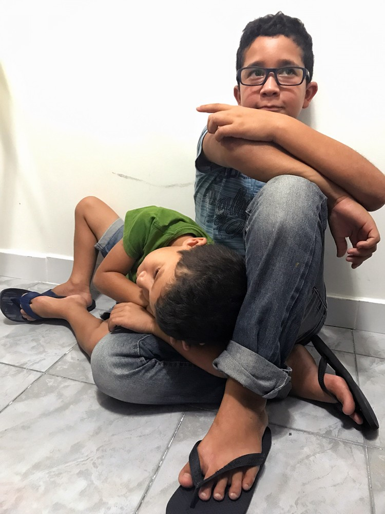 A little boy sits with his right knee jutting out, his arms crossed on his left knee; another little boy rests his head on the first boy's knee
