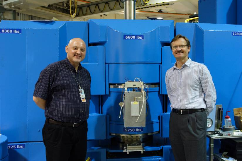 Two men stand beside a large piece of laboratory equipment