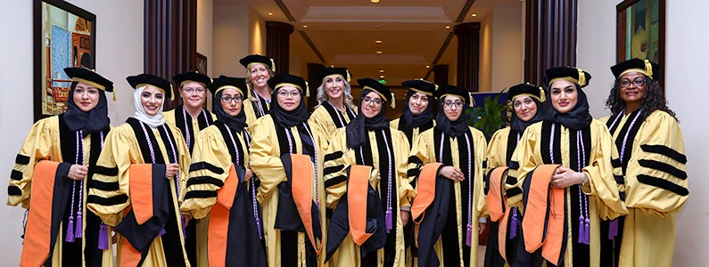 Thirteen women wear commencement regalia, some of whom wear a head covering under their cap