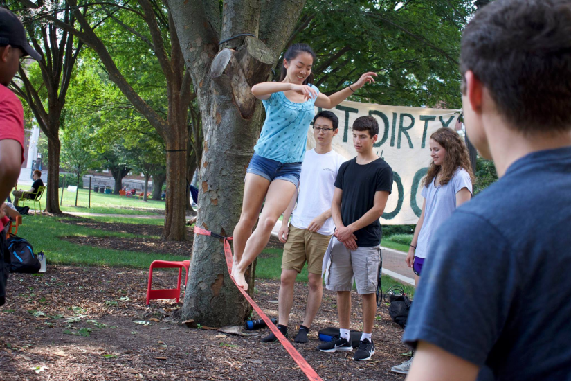 Students from the Johns Hopkins Outdoor Club slackline on campus.