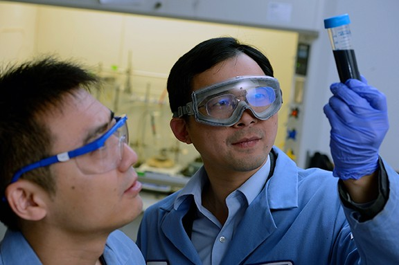 A man wears safety goggles and holds up a test tube with dark liquid and examines it while a second man observes