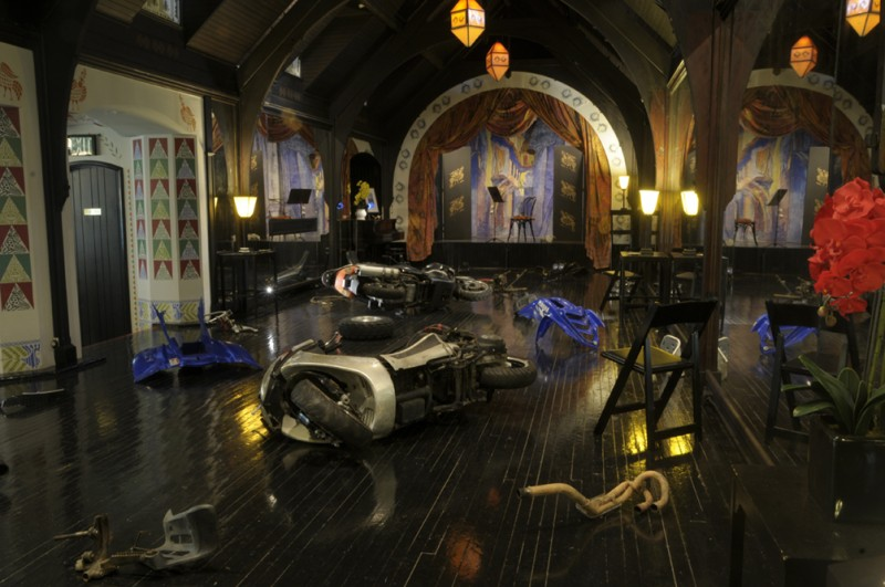 Inside a dimly lit room with gothic features, scooters and dirt bikes are laid on their sides