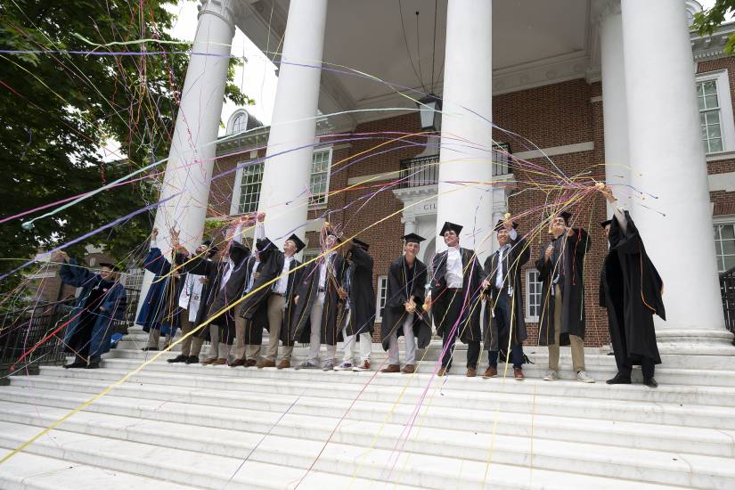 A group of men in Commencement regalia throw streamers