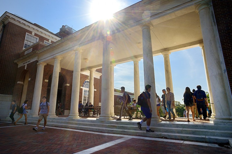 Students walk through the Homewood Campus Breezeway and the sun shines in the background.