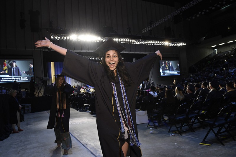 A woman in a graduation cap and gown throws her hands up triumphantly while students cross the stage behind her