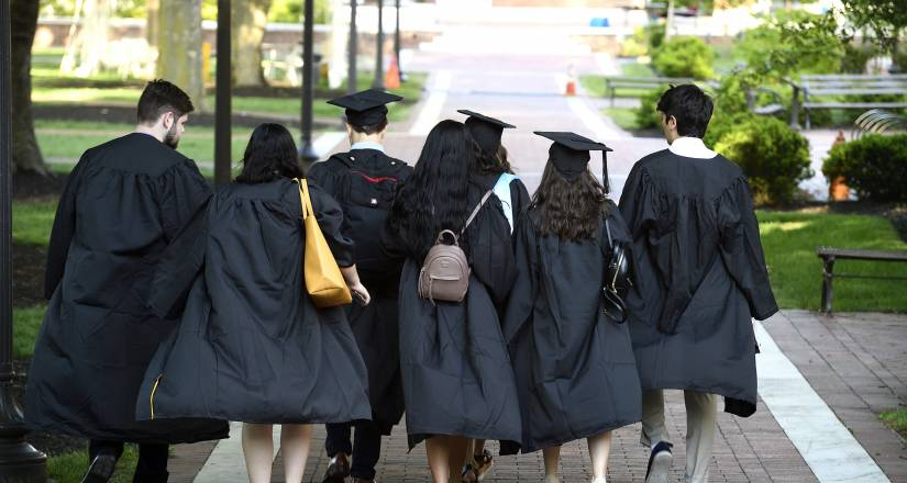 Student walk away from the camera wearing Commencement regalia
