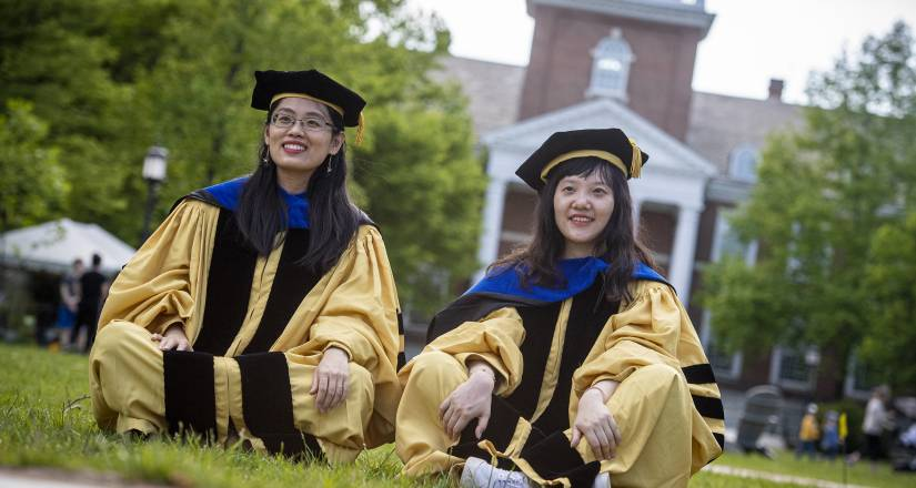 Students in PhD regalia sit in front of Gilman Hall