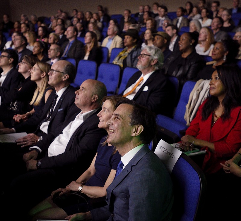 The faces of President Daniels and his wife, Joanna Rosen, are illuminated as they look at a movie screen