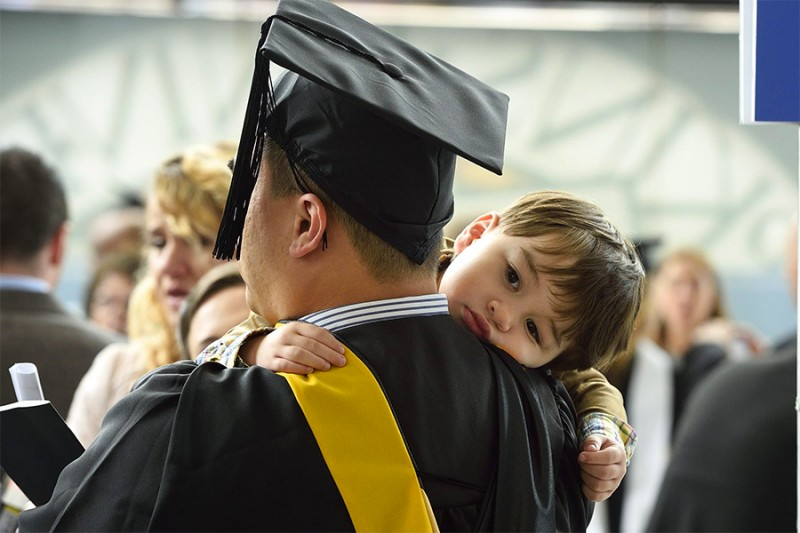 Young boy rests on his father's should during graduation ceremony