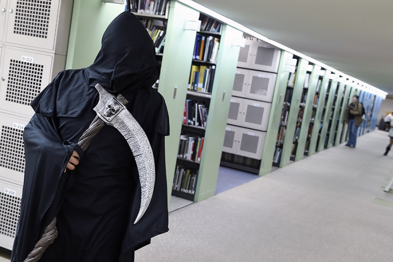 A student is dressed up as the grim reaper against a backdrop of bookcases