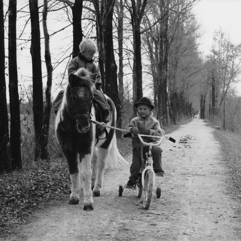 Two boys on the Illinois Prairie Path—one on a bicycle with training wheels, the other on a pony