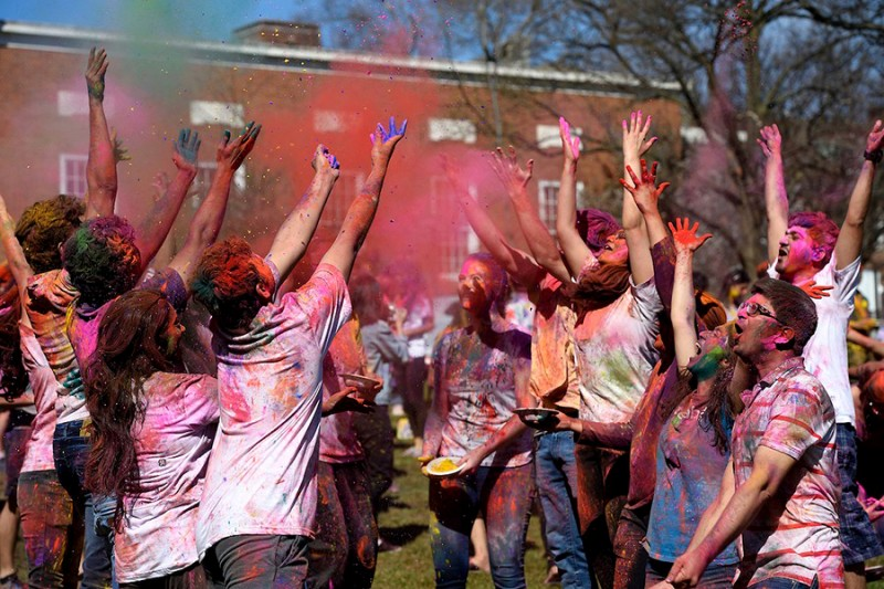 A large group of students wearing clothes covers in colorful powder throw red, green, and pink powder into the air.
