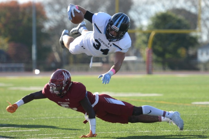 Hopkins player holding football seems to fly over top of a Muhlenberg player who is landing on the ground.