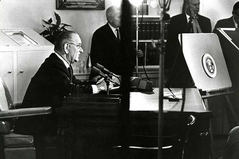 President Johnson sits at desk in Oval Office and prepares to address the nation