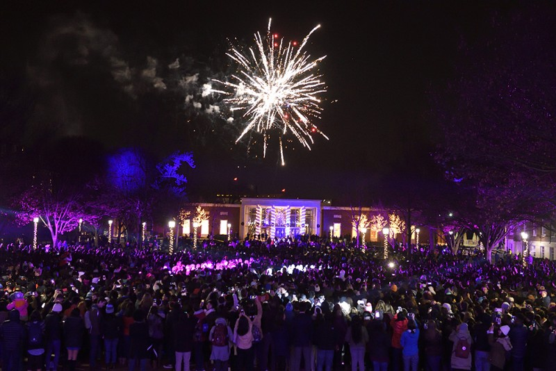 Hundreds of students gather on the quad while the sky lights up with fireworks and laser lights. A campus building in the background glows with holiday lights.