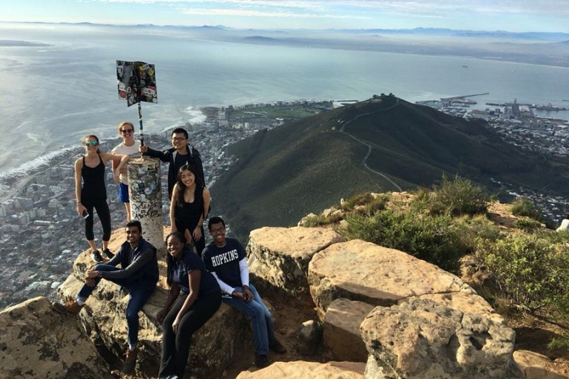Seven students pose around a flag pole at the top of a mountain while a city and coastline sprawls beneath them