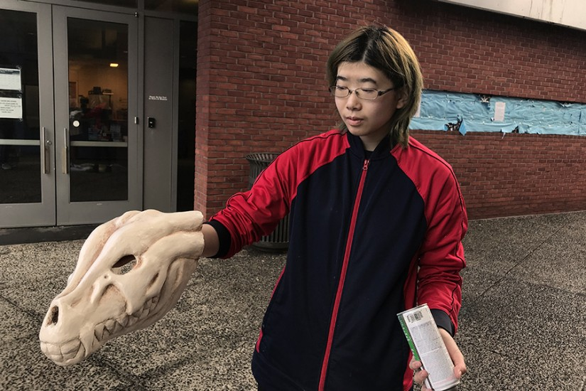 A student holds a mask sculpted to appear like a deer skull