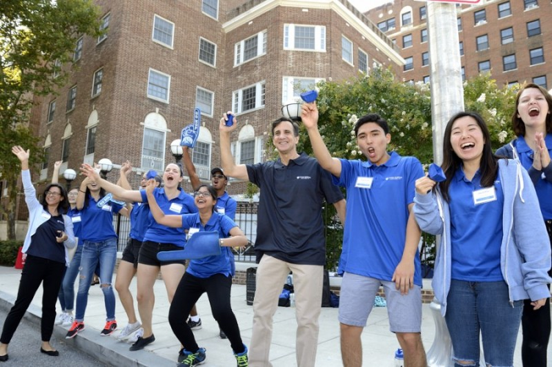 Residence Life staff clad in blue polos excitedly cheer and shake bells as students arrive to campus. JHU President Ronald J. Daniels stands amid them with an equally excited expression.