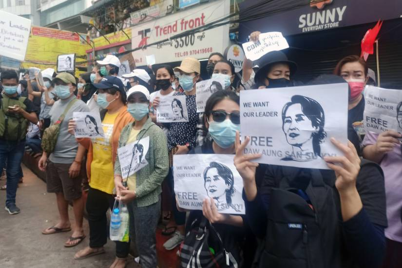 Protesters hold signs calling for release of Aung San Suu Kyi