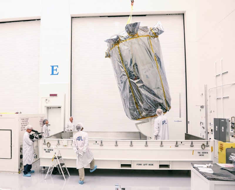 Scientists observe as a giant piece of equipment shrouded in aluminum foil is lifted by crane into a container