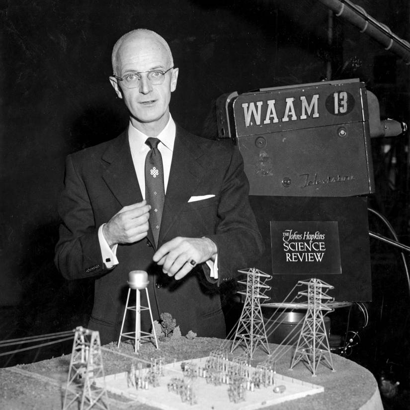 Poole stands over an architectural model
