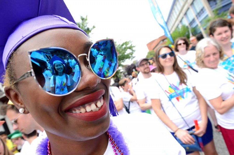 Women wearing purple hat grins with large sunglasses on, in reflection is another woman with a purple graduation hat on and smiling. People in white t-shirt are the background smiling/smirking
