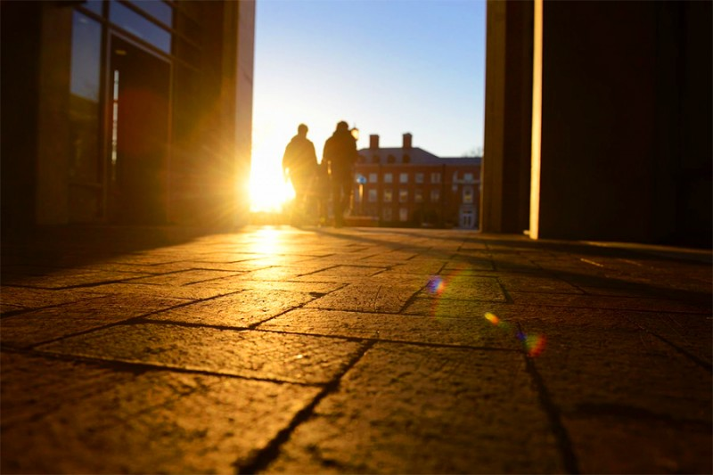 The sun peeks up as two students walk through the breezeway