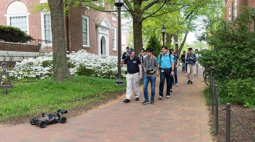 A group walks behind a robot on a brick path
