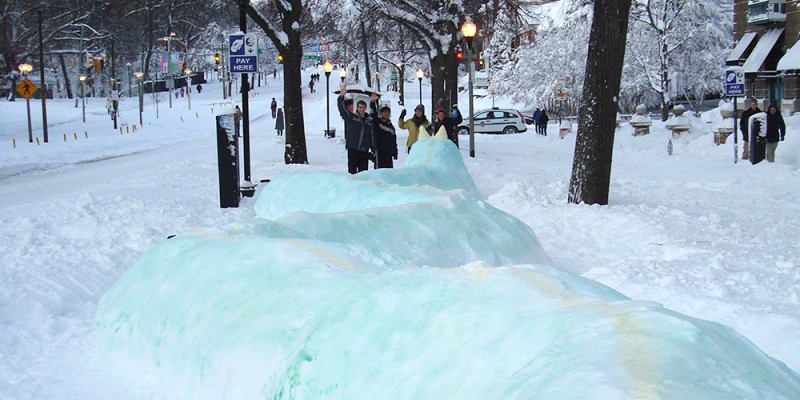 A gigantic snow dragon stretches along the sidewalk in snow-covered Charles Village