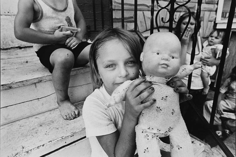 Girl holding doll on stoop