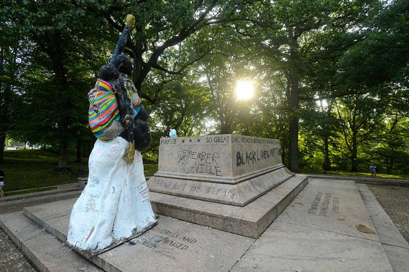 A statue of a woman raising a golden fist in the air and carrying a baby in a sling on her back stands before an empty, vandalized statue base