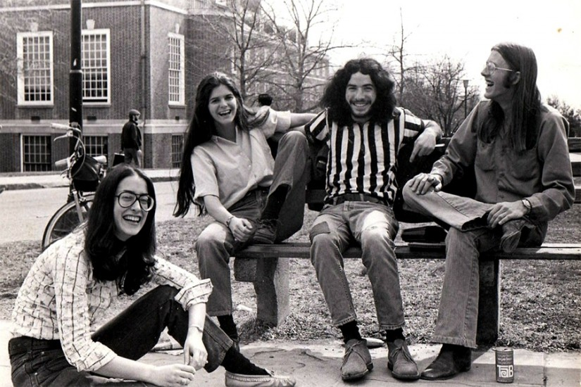 Black and white photo of four students - two male, two female - sitting on a bench