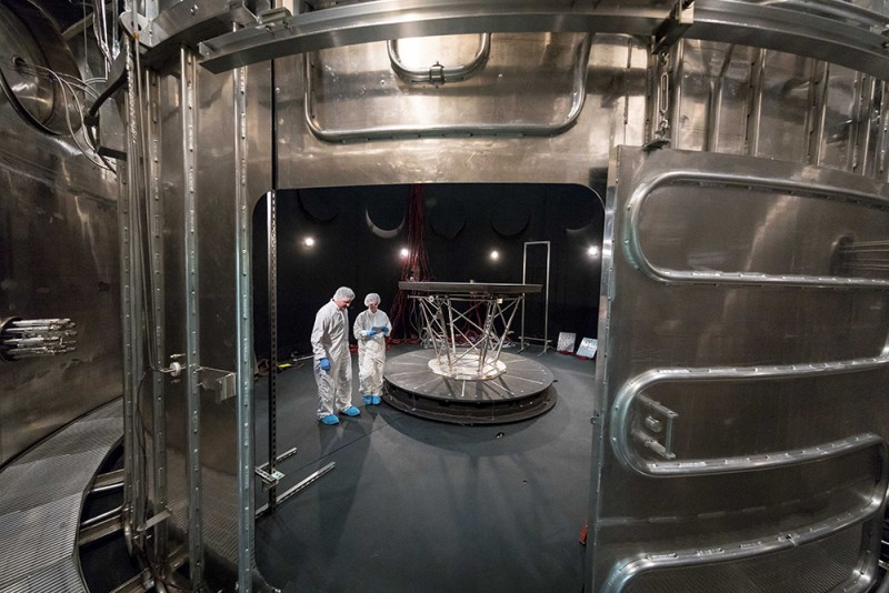 Scientists in lab suits and hair nets stand inside a giant metal vault with a shield bolted to metal brackets inside