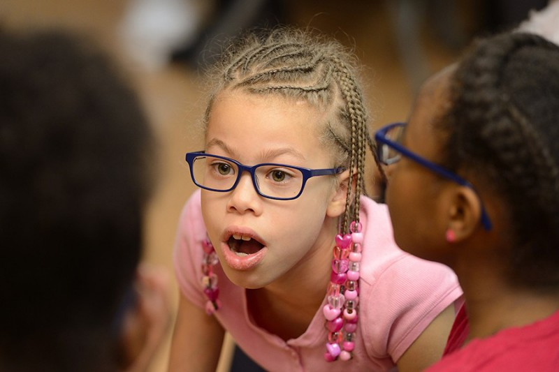 A young girl wearing glasses looks in awe at something outside the line of sight. Her mouth is open in amazement and eyebrows raised.