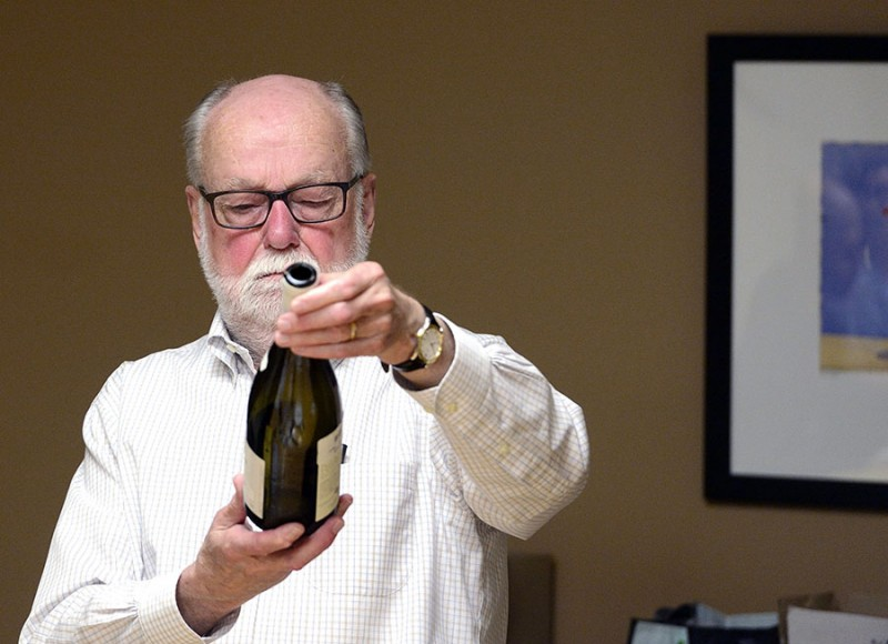 Wine Appreciation instructor looks at the label on a bottle of wine