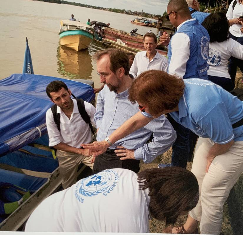 Al Hussein and UN workers stand by a river