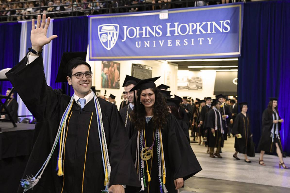 graduates waving to crowd